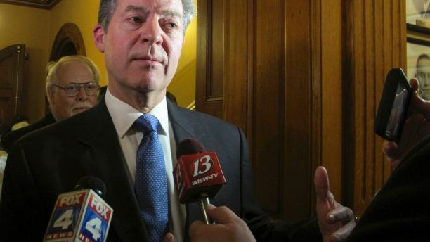In this Jan. 9, 2018 photo, Kansas Gov. Sam Brownback speaks to reporters following his State of the State address, at the Statehouse in Topeka, Kan. Brownback is drawing criticism from fellow Republicans in the Legislature over his budget proposals. (AP Photo/John Hanna)
