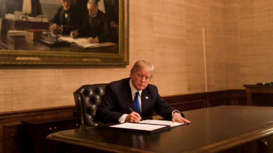 President Trump signs a bill late Monday night in the Treaty Room at the White House. The bill reopens the federal government.